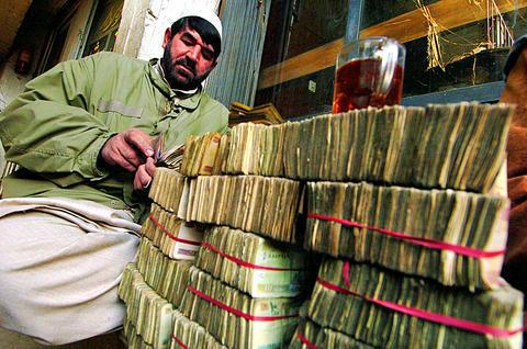 An Afghan money changer near Yaadgar Chowk in Peshawar. (Photo credit: AFP, 2008)