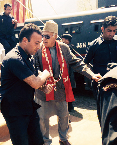 Farooq Abdullah being assisted off the dais by security personnel at Margund in north Kashmir