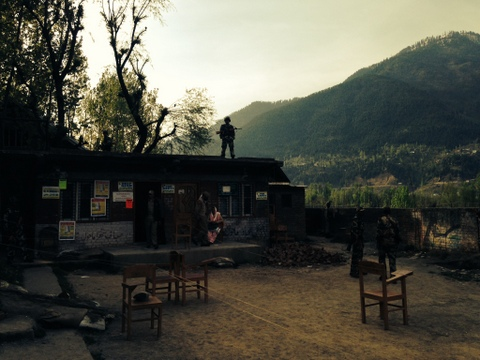 As polling begins for Srinagar, a soldier takes position atop a polling station in the northern rural pocket of Kangan