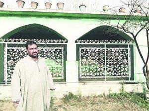 Kuka Parray's elder son Wasim at his graveside in Hajin