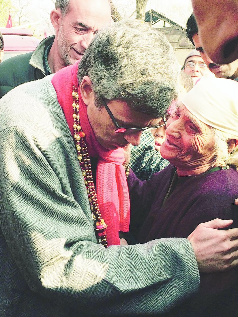 An elderly lady embraces Omar Abdullah on the campaign trail in rural Beerwah
