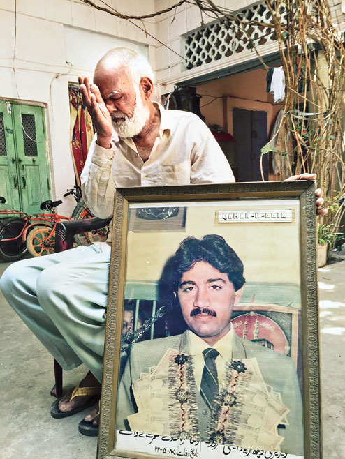 Zamanuddin, Hashimpura victim-survivor, breaks down as he displays a portrait of son Qamruddin who was shot dead by the PAC in May 1987